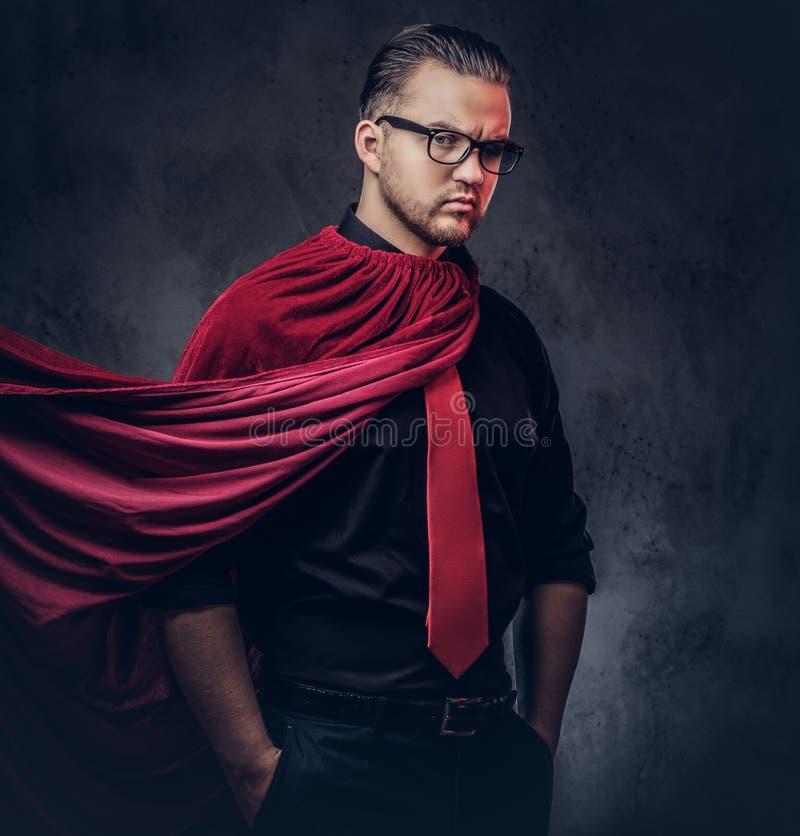 Retrato de un super héroe del malvado del genio en una camisa negra con un lazo rojo fotografía de archivo libre de regalías