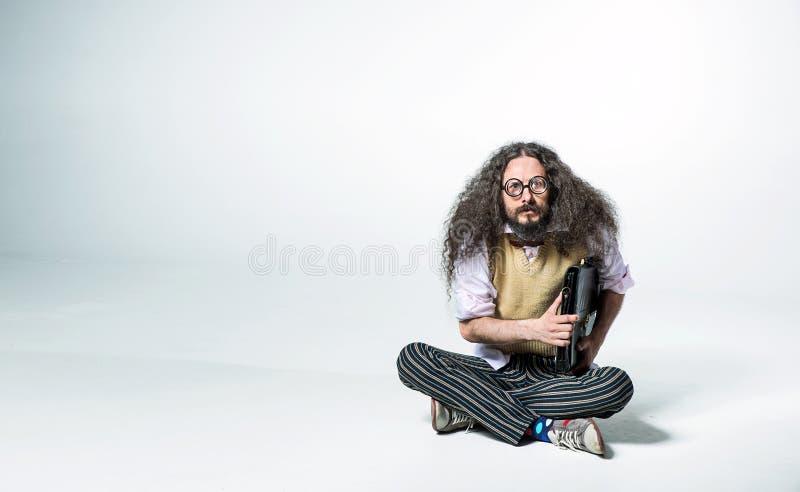 Retrato de un tipo nerd sosteniendo un maletín y sentado en el suelo blanco fotos de archivo libres de regalías