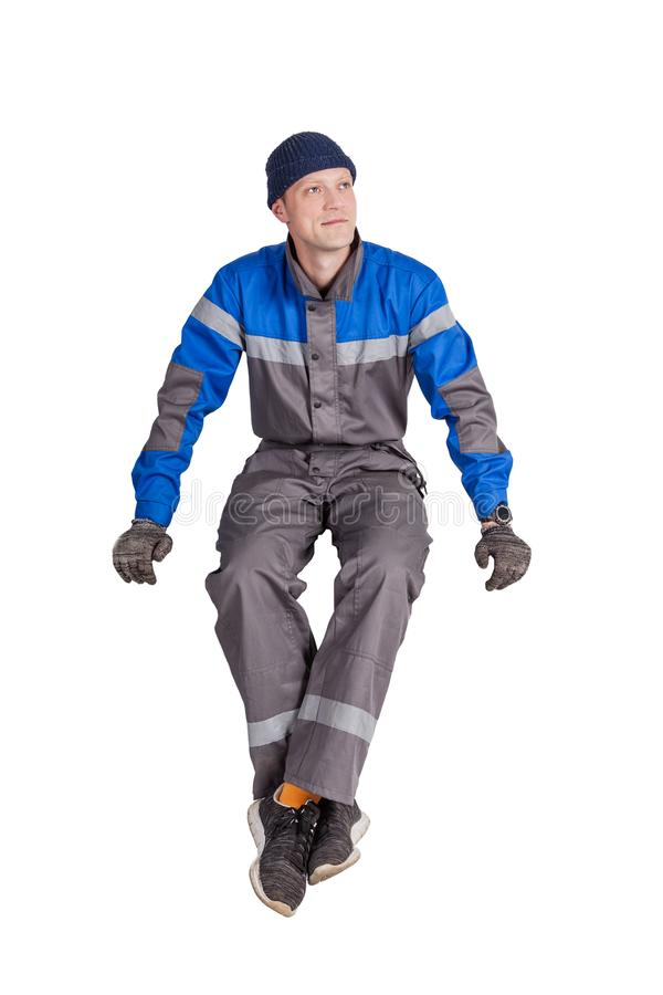 Retrato de un trabajador, de un capataz o de un reparador hermoso de construcción sentándose en un interior blanco imagen de archivo libre de regalías