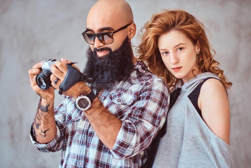 Retrato de un varón barbudo árabe que sostiene una cámara y de su novia hermosa del pelirrojo imagenes de archivo