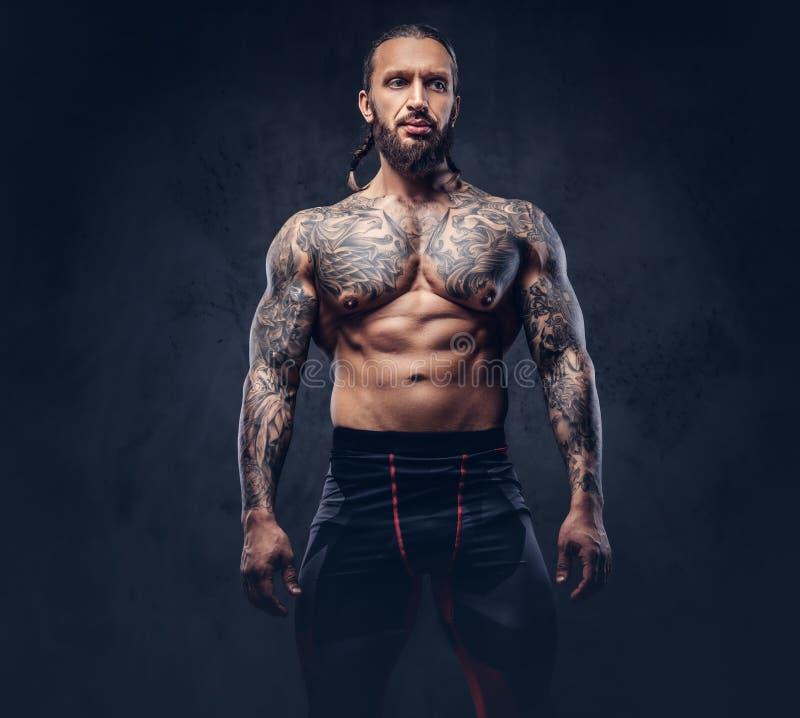 Retrato de un varón tattoed barbudo desnudo muscular con un corte de pelo elegante en pantalones de los deportes, aislado en una  imagenes de archivo