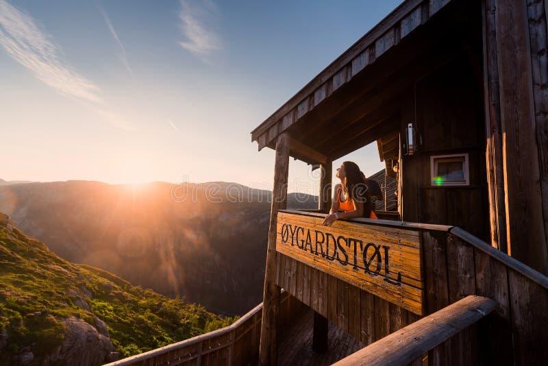 Retrato de un viaje extremo del plan para la muchacha en la piedra del kjerag en las montañas de Noruega, la sensación de foto de archivo libre de regalías