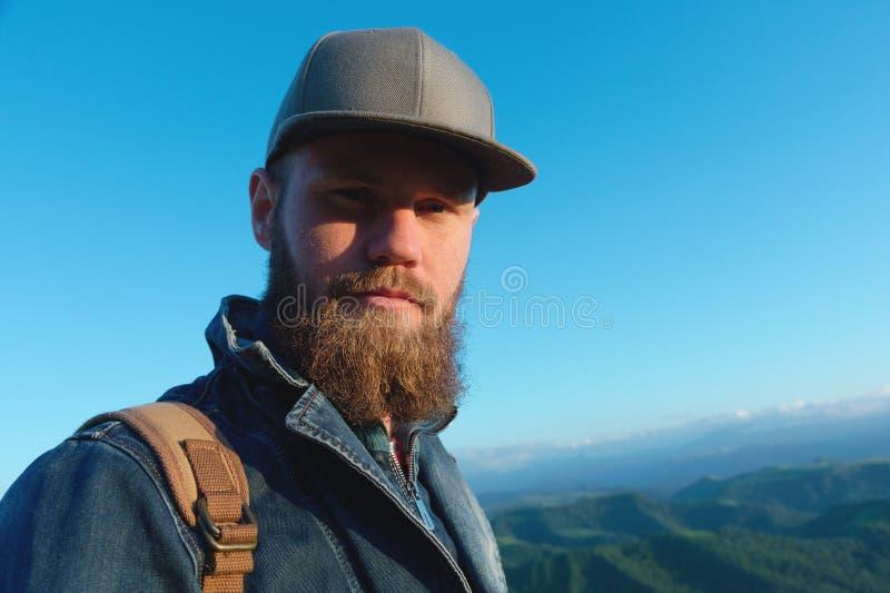 Retrato de un viajero elegante barbudo en un casquillo contra un cielo azul Hora de viajar concepto imagen de archivo libre de regalías