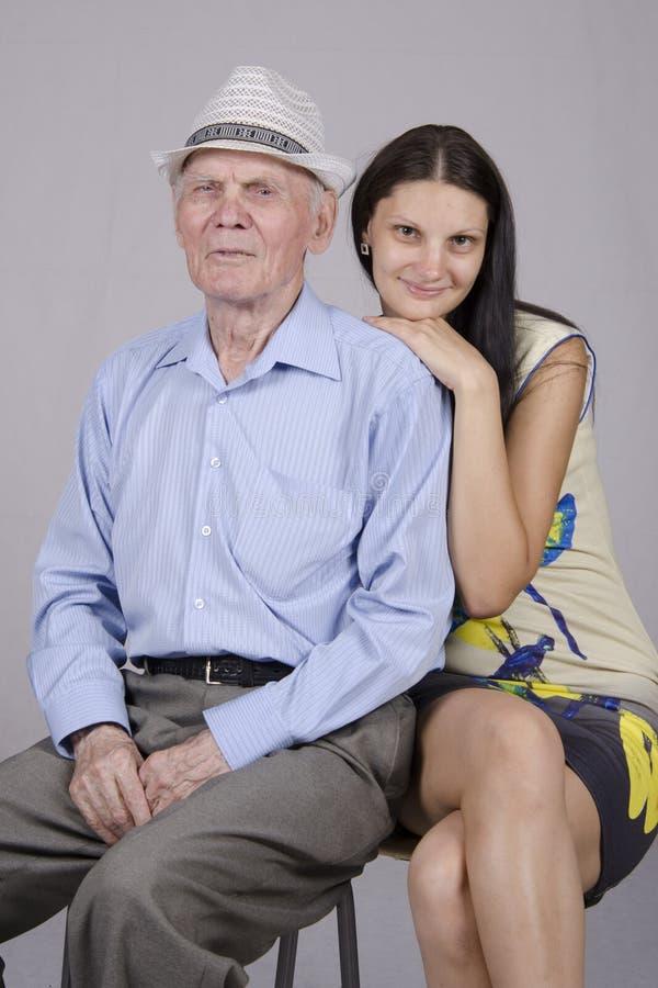 Retrato de un viejo hombre ochenta años con veinte años 'de nieta fotografía de archivo