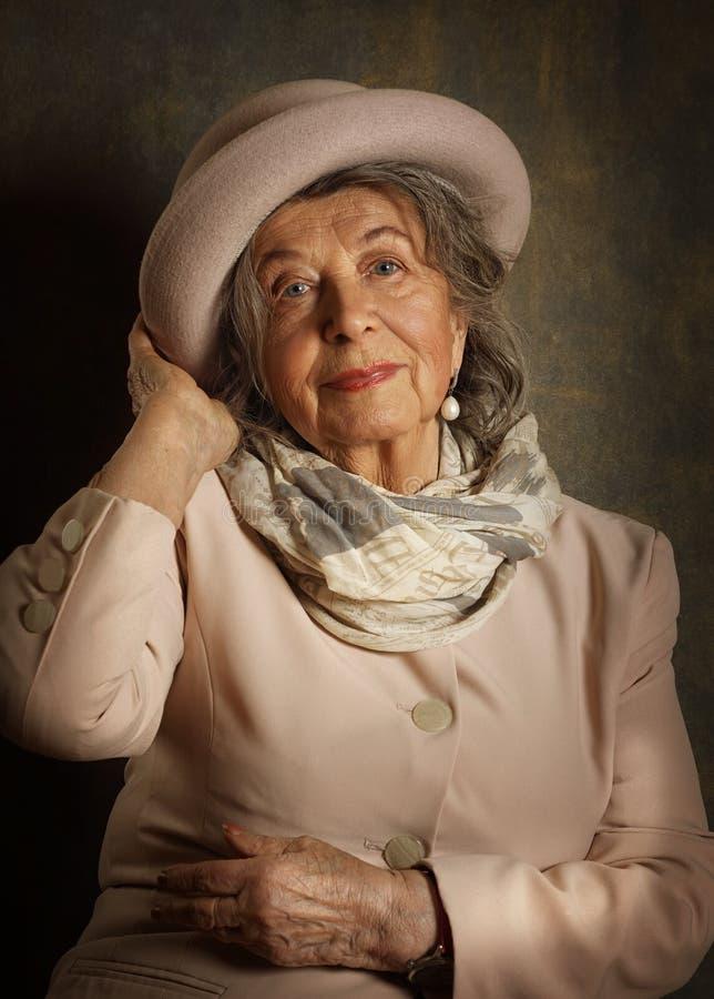 Retrato de una anciana con sombrero y bufanda foto de archivo