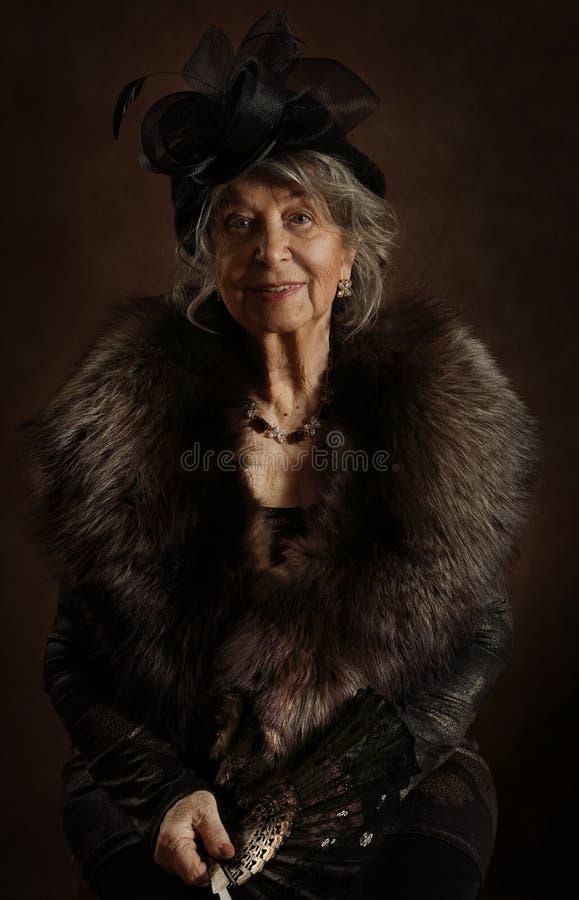 Retrato de una anciana con un fan foto de archivo