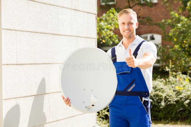 Retrato de una antena parabólica de With TV del técnico foto de archivo libre de regalías