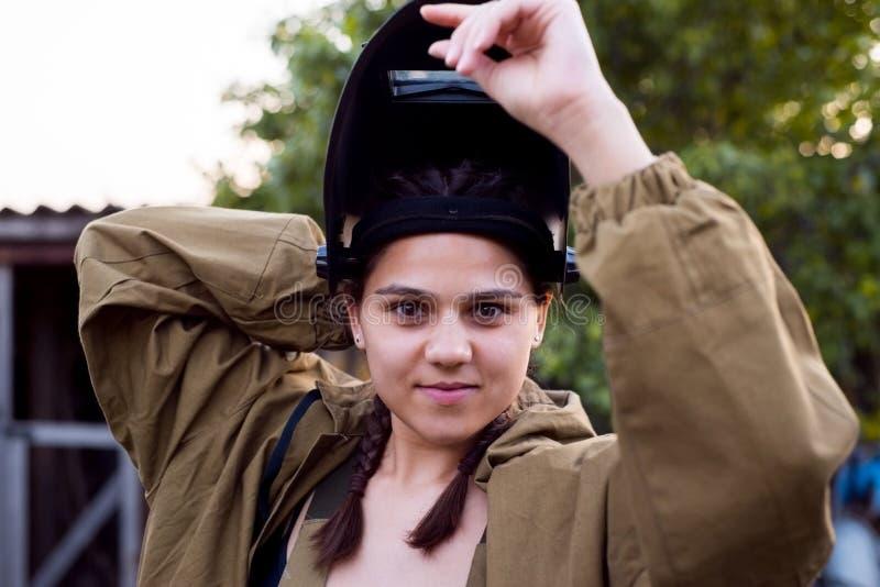 Retrato de una bella joven, unida, en el lugar de trabajo, pone un casco protector para soldar. Mujeres inesperadas foto de archivo