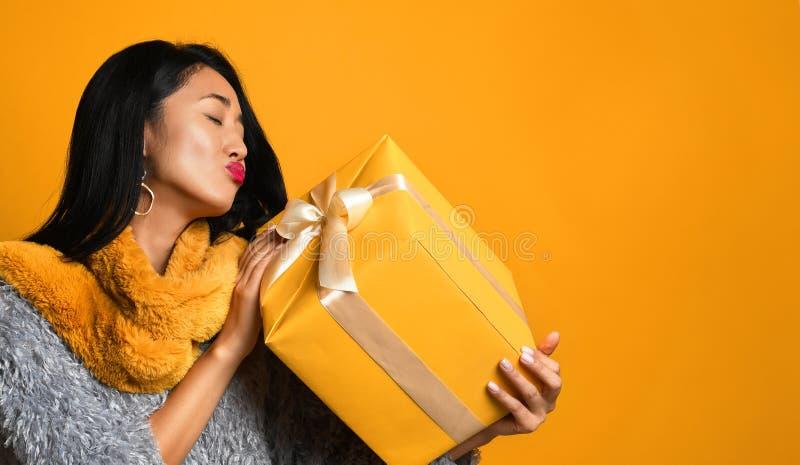 Retrato de una caja de regalo bonita sonriente de la tenencia de la muchacha aislada sobre fondo amarillo foto de archivo libre de regalías