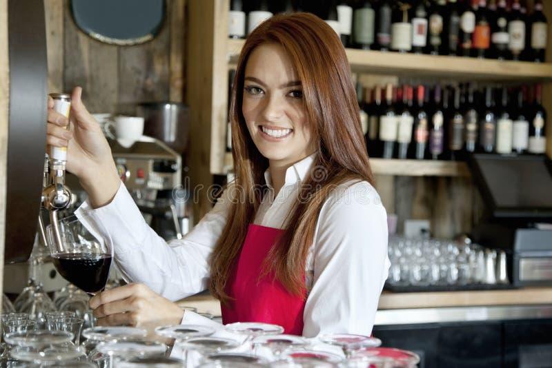 Retrato de una camarera joven hermosa que quita el vino en barra fotografía de archivo