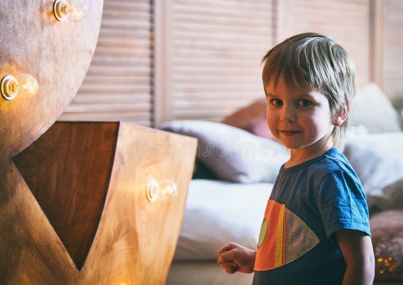 Retrato de una cara sonriente y de mirar del niño pequeño la cámara, niño feliz que se relaja en casa el fin de semana fotos de archivo