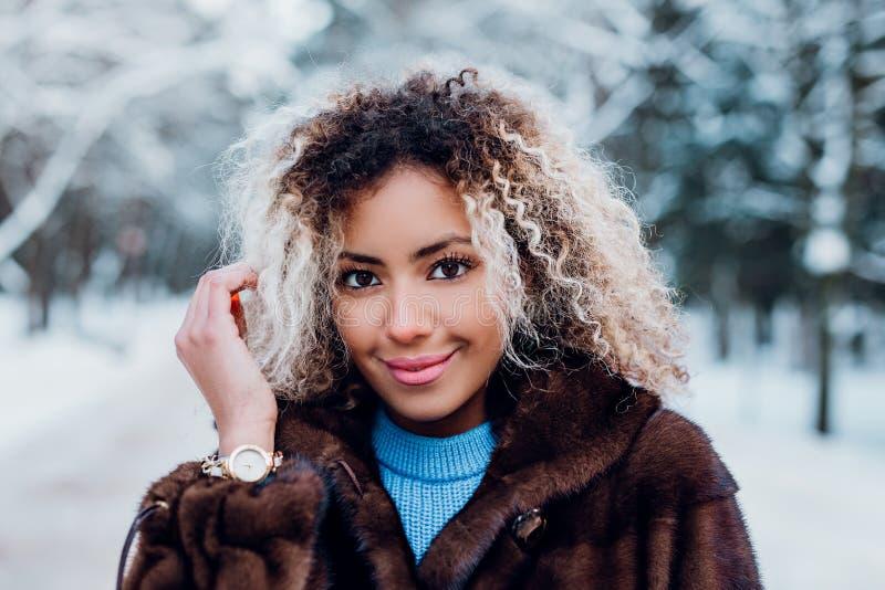 Retrato de una chica afro-americana vestida con abrigo de piel y caminando en un parque de invierno imagen de archivo
