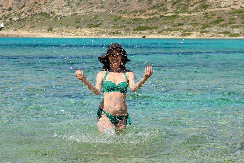 Retrato de una chica joven alegre en un sombrero negro y un traje de baño verde que se colocan en la agua de mar esmeralda y que  foto de archivo libre de regalías