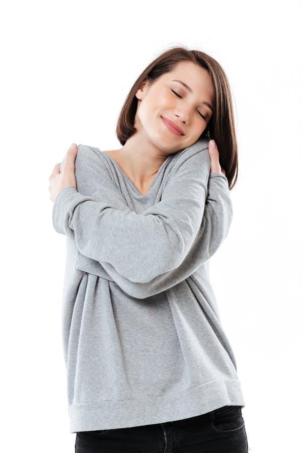 Retrato de una chica joven bonita que se abraza mientras que se coloca imagen de archivo libre de regalías