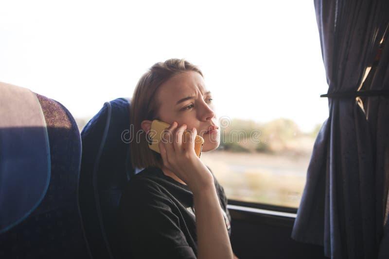 Retrato de una chica joven bonita que se sienta en un autobús y que habla en el teléfono fotografía de archivo