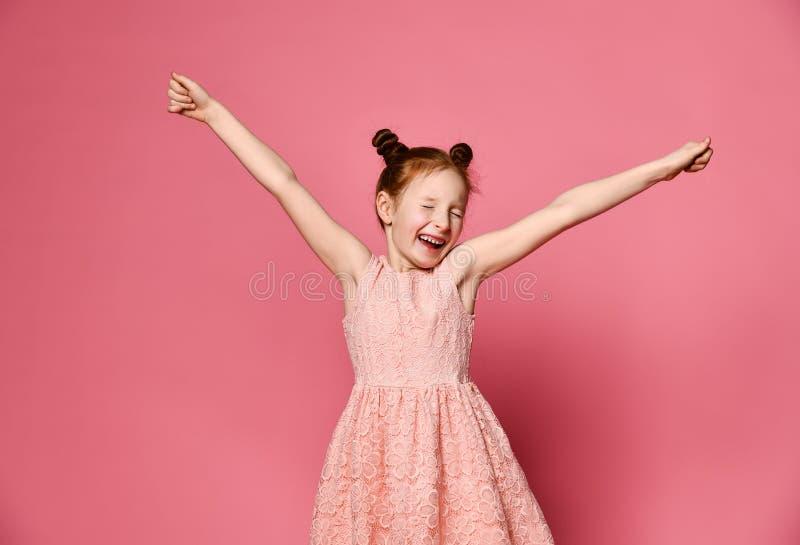 Retrato de una chica joven con el pelo rojo que sonríe en la cámara con las manos en el aire foto de archivo