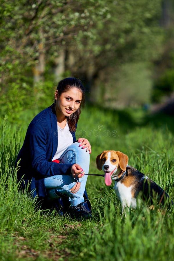Retrato de una chica joven con su perro en el parque imagenes de archivo