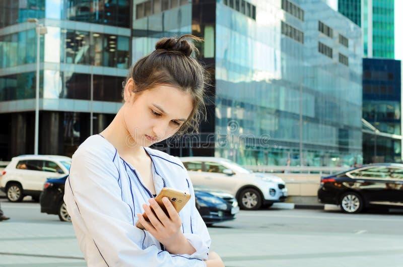 Retrato de una chica joven con un teléfono móvil fotografía de archivo