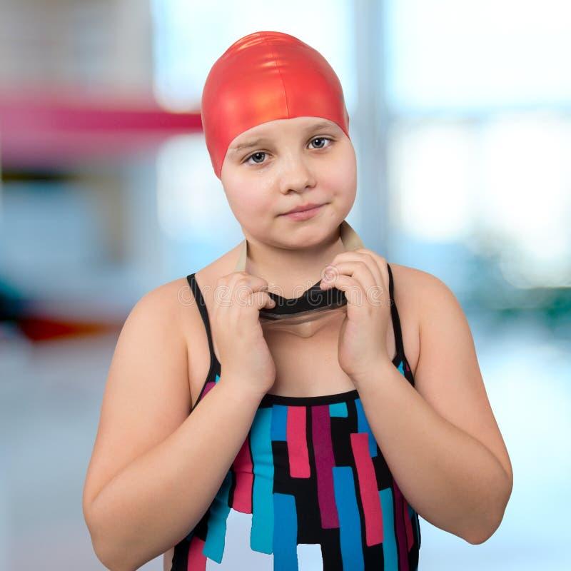 Retrato de una chica joven en un casquillo rojo en la piscina. fotografía de archivo