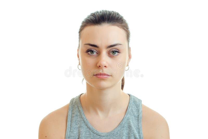 Retrato de una chica joven encantadora sin el maquillaje que mira seriamente la cámara imagen de archivo libre de regalías