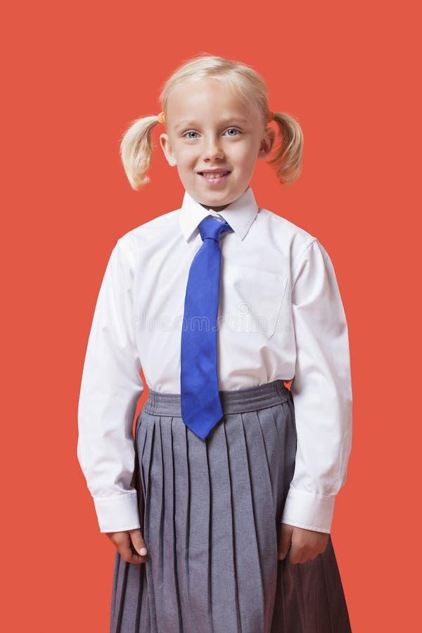 Retrato de una chica joven feliz en uniforme escolar sobre fondo anaranjado foto de archivo