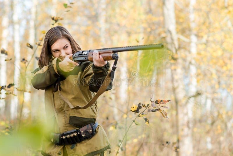 Retrato de una chica joven hermosa en cazador del camuflaje con la escopeta fotografía de archivo libre de regalías