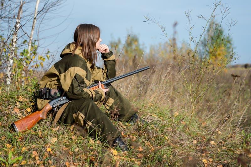 Retrato de una chica joven hermosa en cazador del camuflaje con la escopeta imágenes de archivo libres de regalías