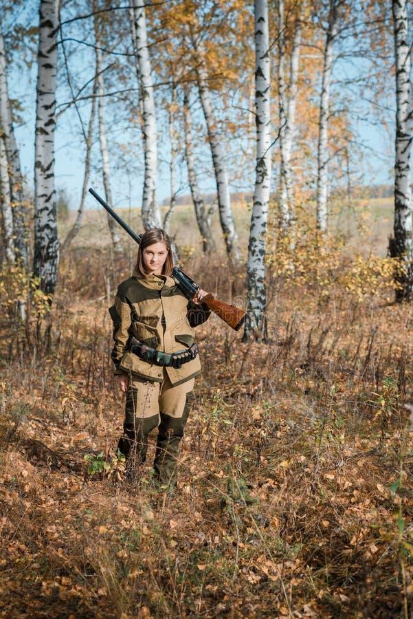 Retrato de una chica joven hermosa en cazador del camuflaje con la escopeta imagenes de archivo