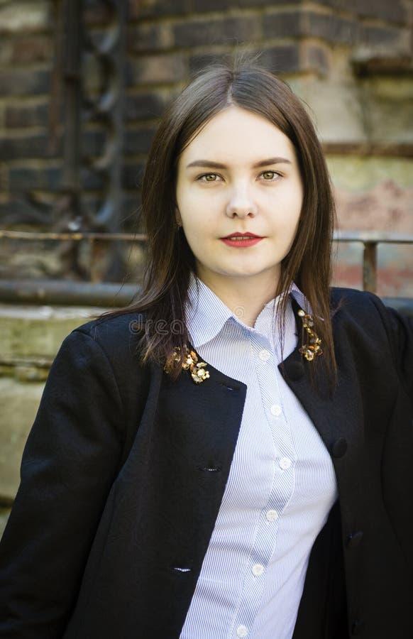 Retrato de una chica joven hermosa en una chaqueta negra fotografía de archivo