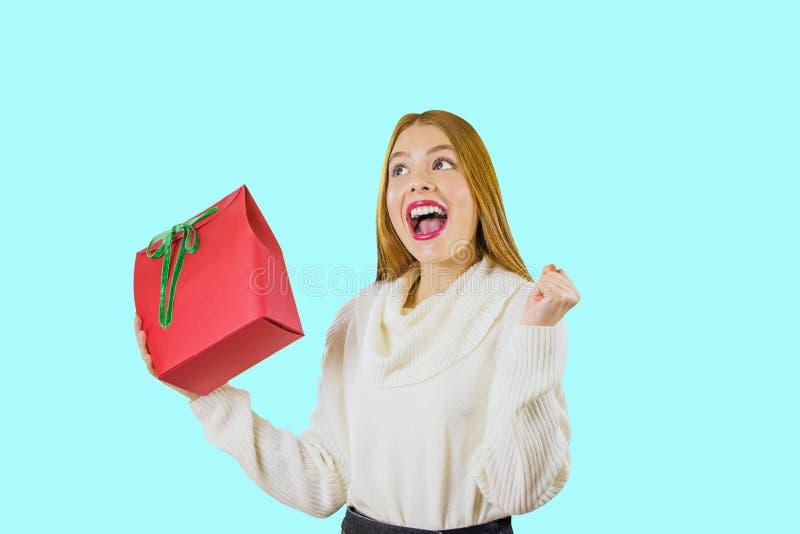 Retrato de una chica joven pelirroja que sostiene un regalo en su mano y que aumenta su otra mano con un puño apretado y imagen de archivo