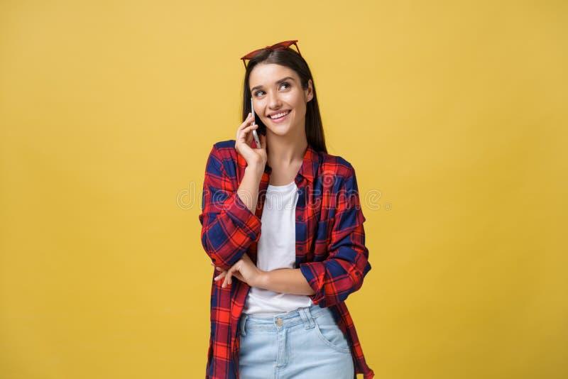 Retrato de una chica joven pensativa que invita al teléfono móvil mientras que se coloca y parece lejos aislado sobre fondo amari foto de archivo libre de regalías