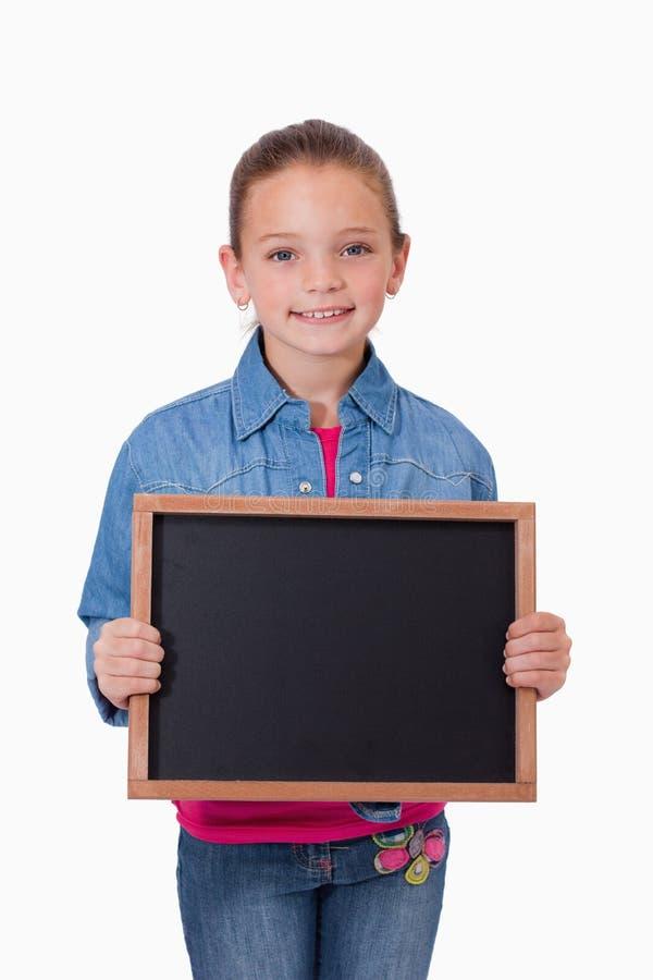 Retrato de una chica joven que sostiene una pizarra de la escuela fotos de archivo