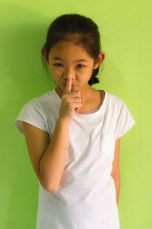 Retrato de una chica joven sonriente con su finger sobre su boca foto de archivo