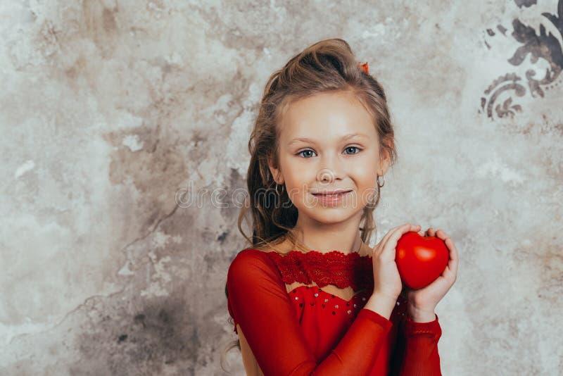 Retrato de una chica joven sonriente en un vestido rojo y con un peinado hermoso con un coraz?n imagen de archivo libre de regalías