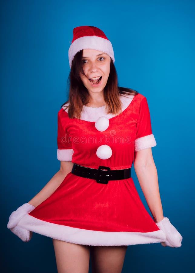 Retrato de una chica joven vestida como Santa Claus en un fondo azul ¡Feliz Año Nuevo y Feliz Navidad! imagen de archivo