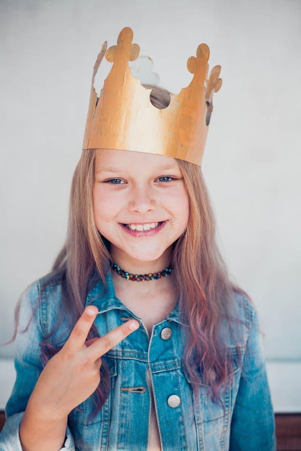 Retrato de una colegiala con el pelo de color vestido con corona dorada y que muestra la victoria o la señal del dedo de la paz fotografía de archivo libre de regalías