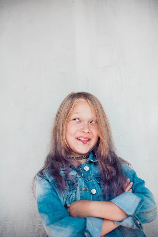 Retrato de una colegiala linda con el pelo largo y colorido haciendo caras graciosas fotos de archivo libres de regalías