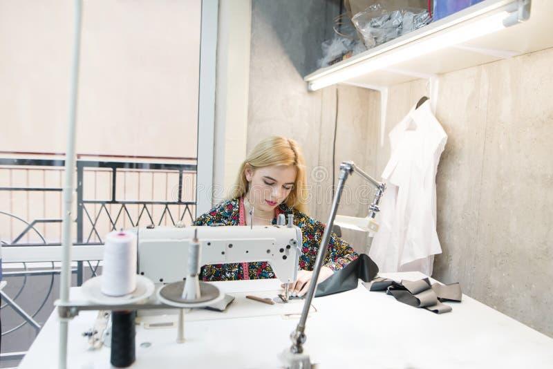 Retrato de una costurera joven en el trabajo sobre una máquina de coser profesional Costurera atractiva en el trabajo en el estud imagenes de archivo