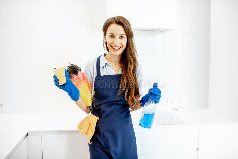 Retrato de una criada joven con las herramientas de limpieza en casa fotografía de archivo libre de regalías