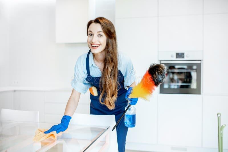 Retrato de una criada joven con las herramientas de limpieza en casa fotos de archivo