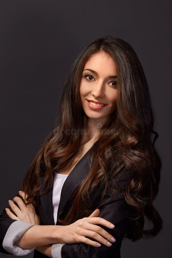 Retrato de una empresaria atractiva que se coloca con sus brazos cruzados fotos de archivo