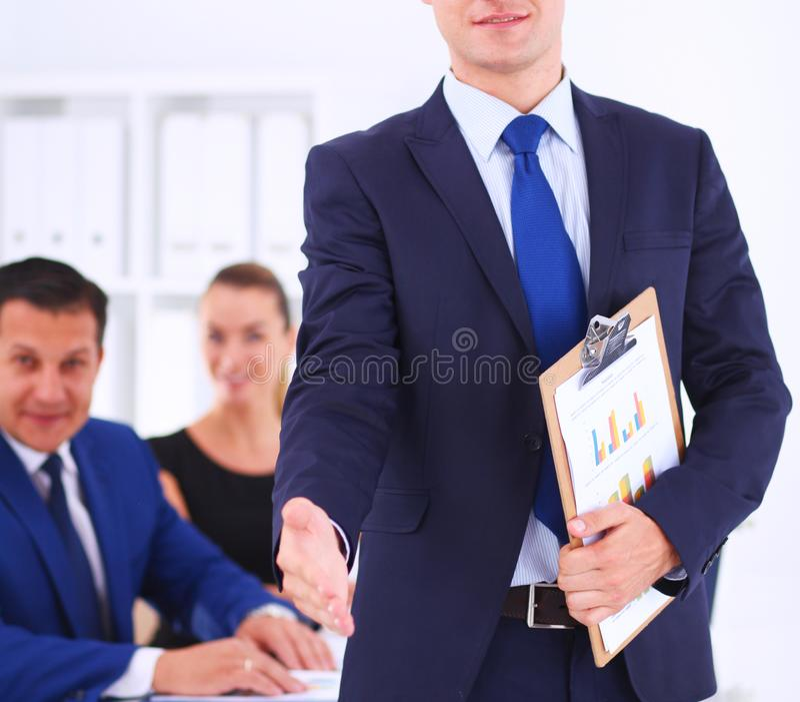 Retrato de una empresaria hermosa que se coloca en oficina con los colegas fotos de archivo