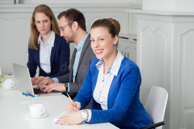 Retrato de una empresaria joven que toma notas durante el meetin fotografía de archivo