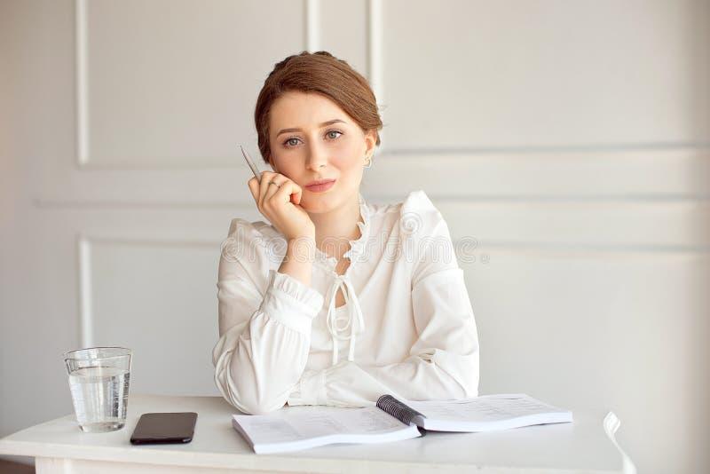 Retrato de una empresaria morena joven sonriente hermosa en una camisa blanca que se sienta en un puesto de trabajo moderno brill imagenes de archivo