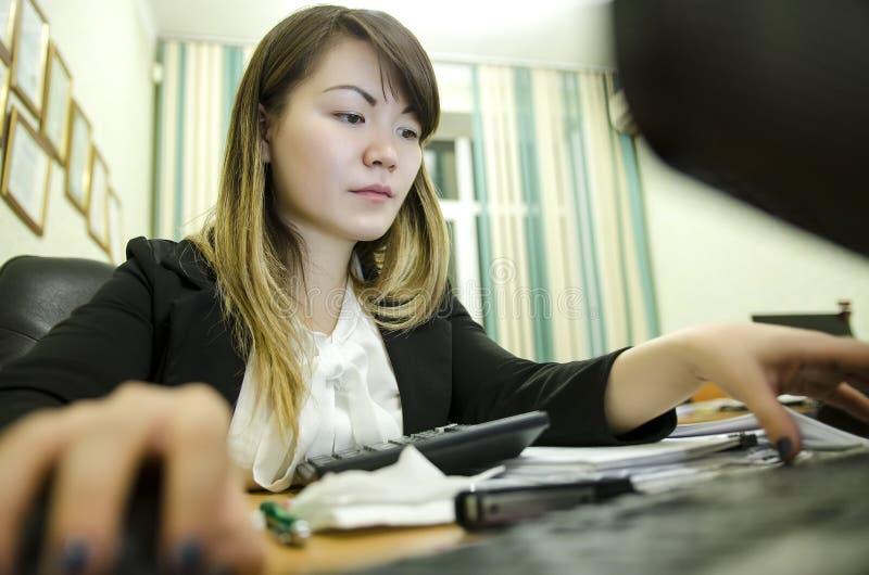 Retrato de una empresaria que se sienta en su lugar de trabajo en la oficina, el mecanografiar, mirando la pantalla de la PC foto de archivo libre de regalías