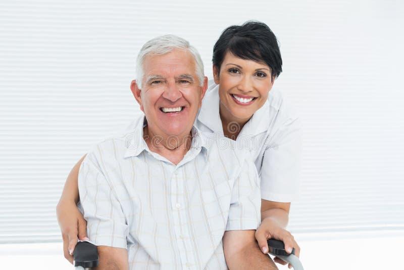 Retrato de una enfermera con el paciente mayor que se sienta en silla de ruedas foto de archivo