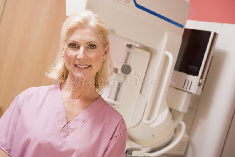 Retrato de una enfermera con la máquina del mamograma fotografía de archivo