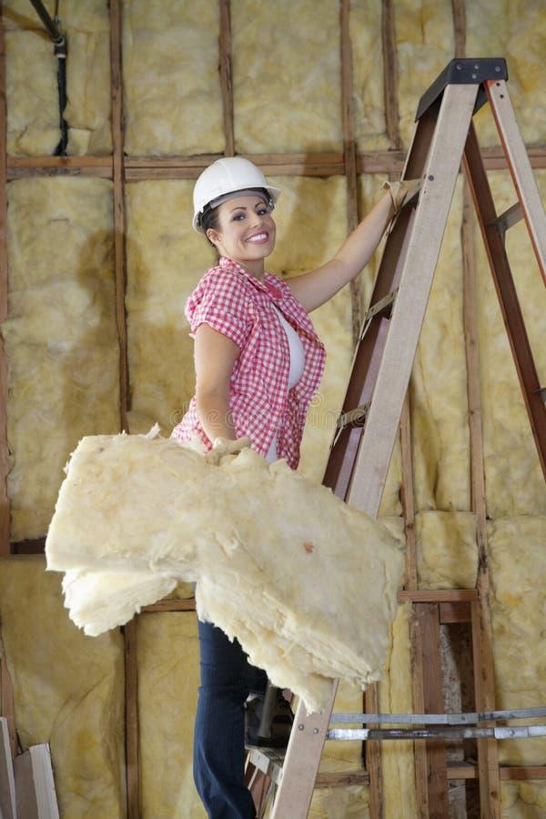 Retrato de una esponja que lleva femenina feliz del trabajador de construcción mientras que sube la escalera imagenes de archivo