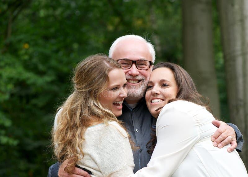 Retrato de una familia feliz con el padre y dos hijas imagen de archivo