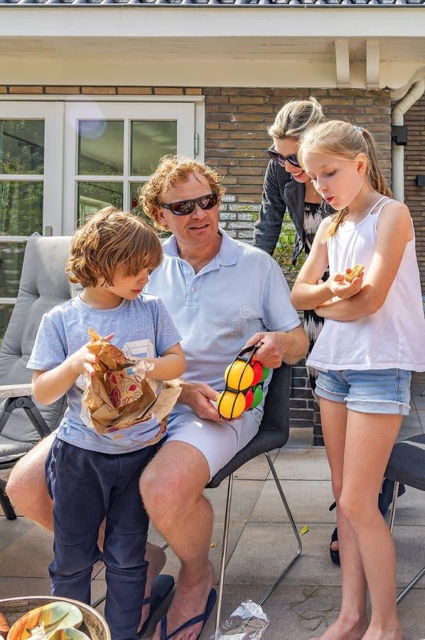 Retrato de una familia feliz en el jardín Un niño pequeño coge su presente de cumpleaños, su padre, madre, y la hermana admira el imagenes de archivo